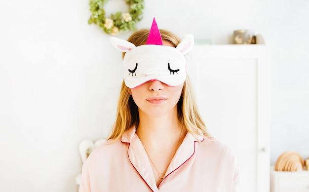 Giovane donna in maschera di sonno unicorno e pigiama rosa in posa sullo sfondo della camera da letto.