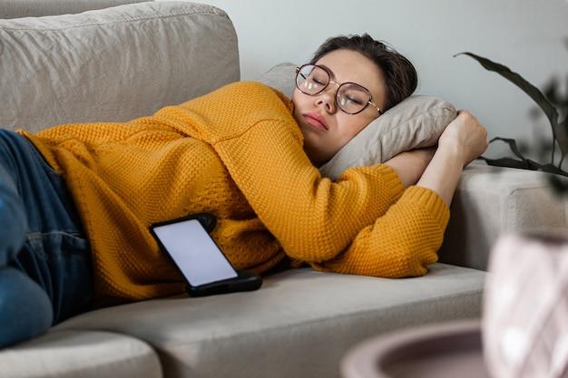 La giovane donna dorme sul divano usando il cellulare