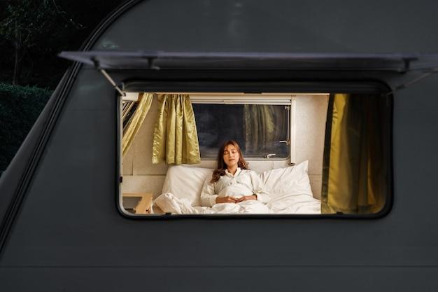 Giovane donna che dorme sul letto di un camper rv van motorhome