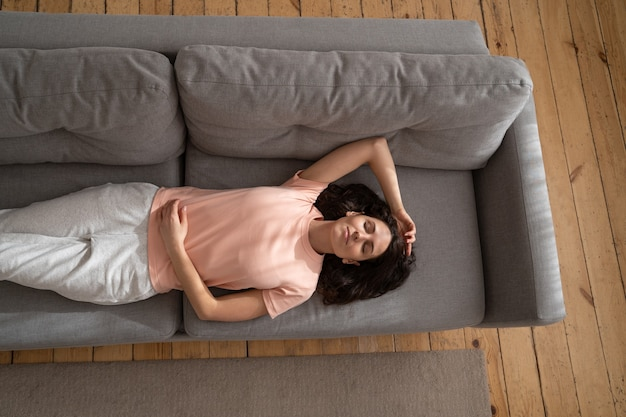 Giovane donna che dorme sul divano con il braccio in alto a casa, chiudendo gli occhi e prendendo una pausa, vista dall'alto.