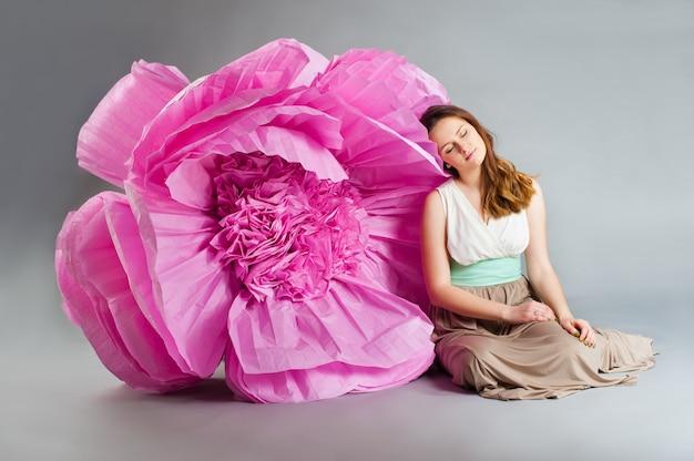 Giovane donna che dorme vicino a un fiore enorme