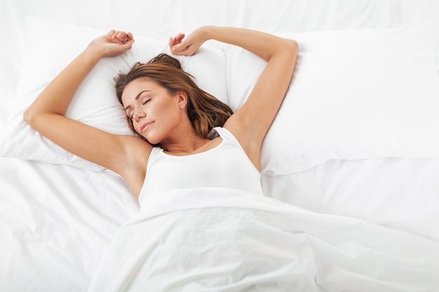 Giovane donna che dorme sul lino bianco nel letto di casa