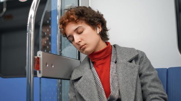 La giovane donna dorme durante un viaggio mattutino in metropolitana