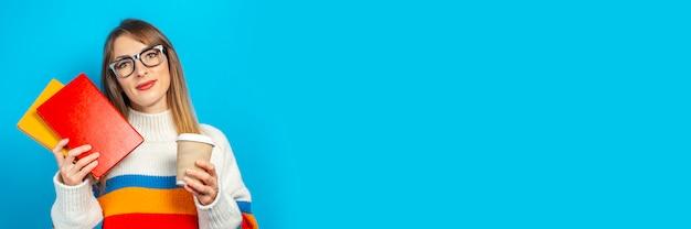La giovane donna sorride e tiene i libri e un bicchiere di caffè o un tè in sue mani su una priorità bassa blu. concetto di educazione, college, sessione, esame, scelta di carriera. bandiera