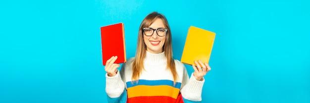 La giovane donna sorride e tiene i libri in sue mani su una priorità bassa blu. concetto di educazione, college, sessione, esame, scelta di carriera. bandiera