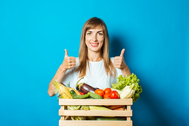 La giovane donna sorride e tiene una scatola con gli ortaggi freschi sul blu. buon concetto di vendemmia, prodotto naturale