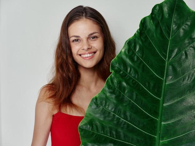 La giovane donna sorride e sta dietro una foglia verde di una palma su uno sfondo chiaro esotico pulito