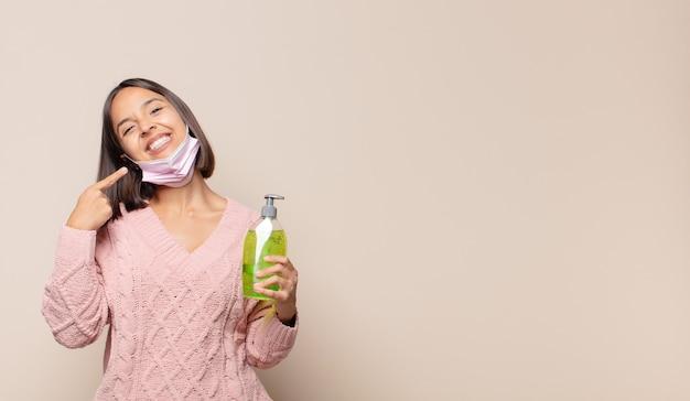 Giovane donna che sorride fiduciosamente indicando il proprio ampio sorriso, atteggiamento positivo, rilassato, soddisfatto