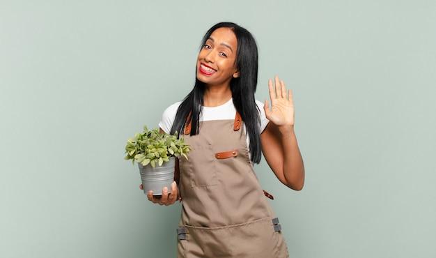 Giovane donna che sorride allegramente e allegramente, agitando la mano, dandoti il benvenuto e salutandoti o salutandoti