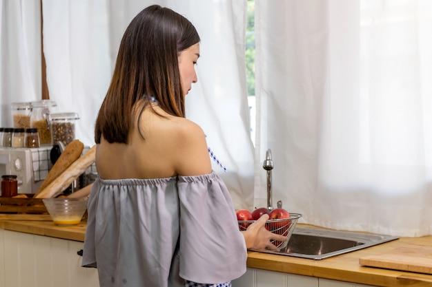 Giovane donna che sorride e che tiene il canestro della mela nella cucina.