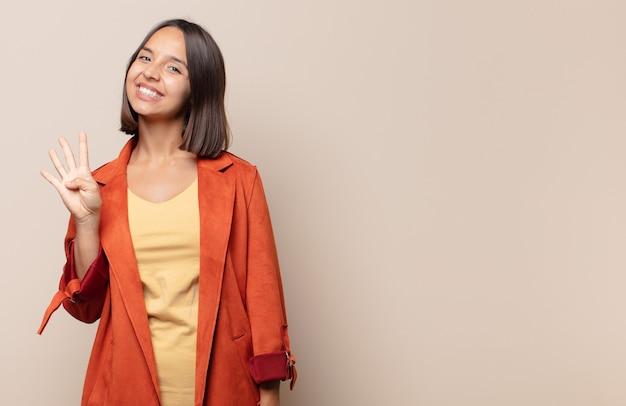 Giovane donna sorridente e dall'aspetto amichevole, mostrando il numero quattro o quarto con la mano in avanti, conto alla rovescia
