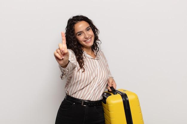 Giovane donna sorridente e dall'aspetto amichevole, mostrando il numero uno o il primo con la mano in avanti, il conto alla rovescia