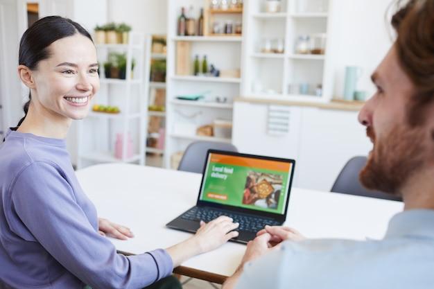 Giovane donna che sorride all'uomo e che fa la consegna del cibo sul laptop mentre sono seduti al tavolo in cucina