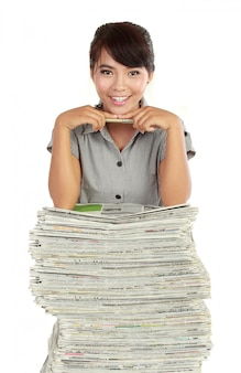 Giovane donna che sorride, con molto giornale