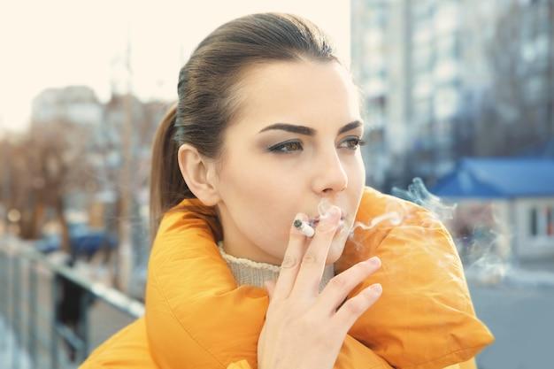 Giovane donna che fuma sigaretta, all'aperto