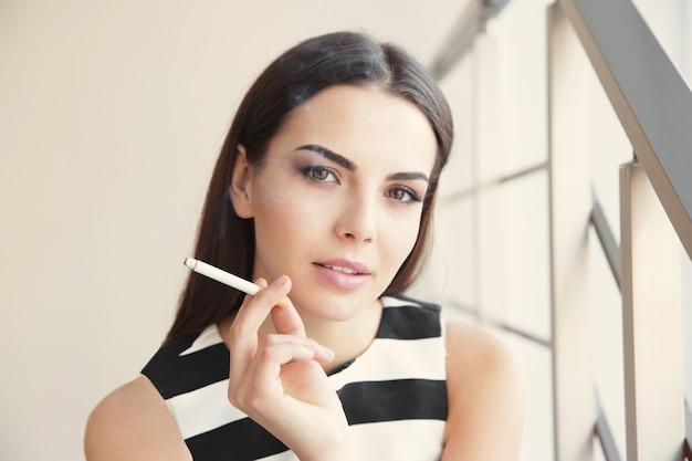 Giovane donna che fuma sigaretta su scale