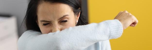 La giovane donna starnutisce nel suo primo piano del gomito