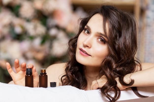 La giovane donna annusa gli aromi degli oli naturali. una bella mora è seduta in un bagno bianco.
