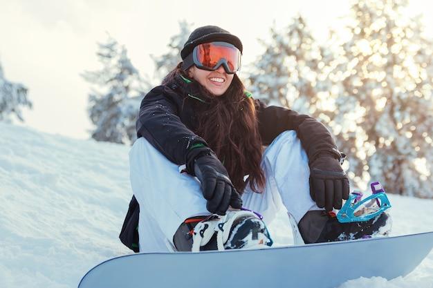Lo snowboarder della giovane donna è sorridente e seduto sulla neve della montagna