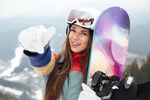 Giovane donna snowboarder sulle piste gelida giornata invernale che tiene lo snowboard in mano e fa il gesto del pollice in alto