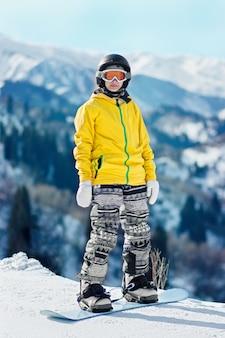 Snowboarder di giovane donna in giacca gialla e casco nero sullo sfondo di montagne innevate