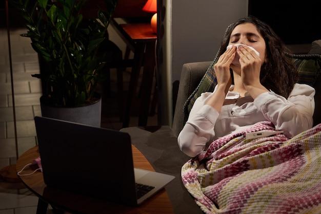 Giovane donna sul divano coperto con una coperta che soffia il naso che cola che soffre ha la febbre