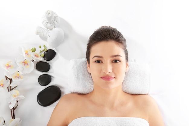 Giovane donna e accessori spa su bianco, vista dall'alto