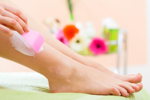 Giovane donna nella stazione termale che ottiene le gambe crema per la depilazione