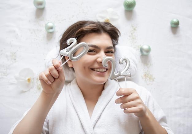 Giovane donna nel salone della stazione termale con il concetto di festa di natale di vista superiore di numeri