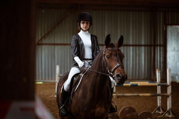 Giovane donna in uniforme speciale e casco da equitazione. sport equestre