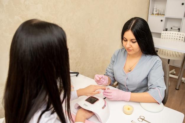 Specialista della giovane donna in manicure che fa massaggio alle mani con crema