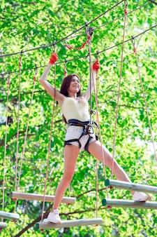 La giovane donna trascorre il tempo libero in un percorso di corde. donna impegnata nel parco di corda.