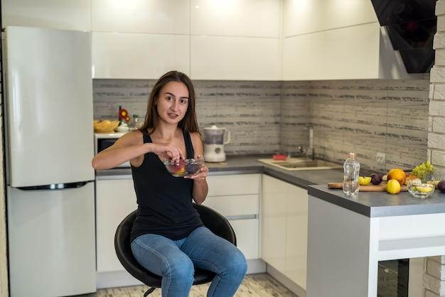 Giovane donna in abiti sportivi con frutta a casa. uno stile di vita sano