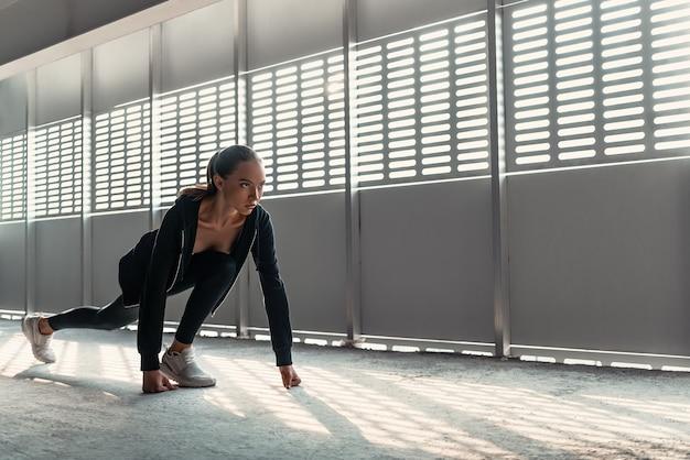 La giovane donna in abiti sportivi sta facendo esercizi di riscaldamento vicino allo stadio. allungamento delle gambe