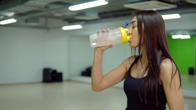 Giovane donna in uniforme sportiva beve acqua in palestra