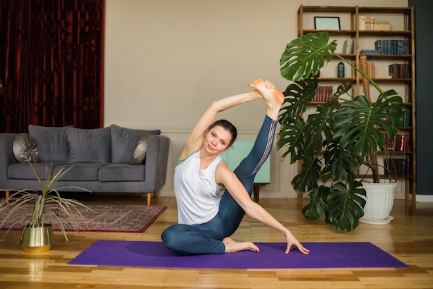 Giovane donna in uniforme sportiva esegue asana su una stuoia di yoga in camera