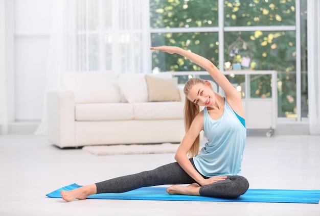 Giovane donna in abiti sportivi facendo esercizi al chiuso