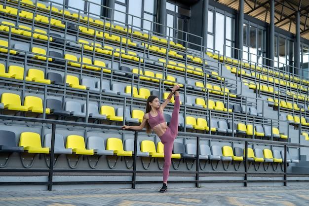 Giovane donna in abiti sportivi che fa spago vicino alle sedie dello stadio. uno stile di vita sano