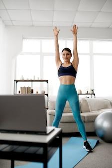 Giovane donna in abiti sportivi a casa, formazione in linea in forma al computer portatile. persona di sesso femminile che fa esercizio fisico, allenamento sportivo internet, interno della stanza