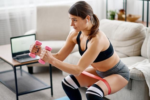 Giovane donna in abiti sportivi a casa, formazione in linea in forma al computer portatile