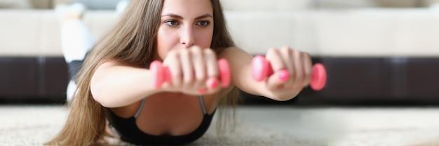Giovane donna in abiti sportivi sdraiata sul pavimento e tenendo i manubri nelle sue mani