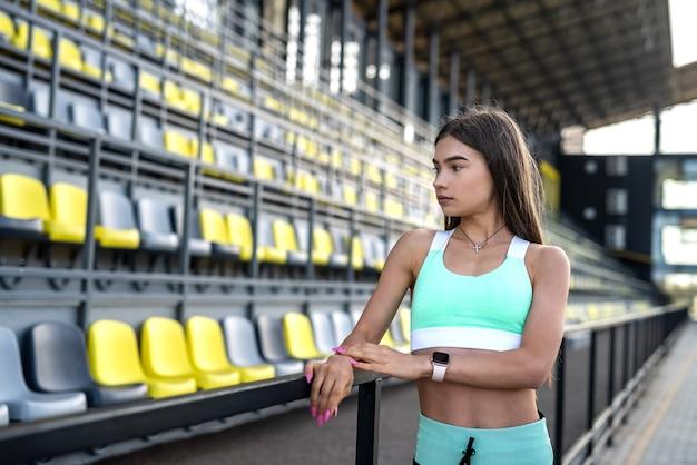 La giovane donna in abbigliamento sportivo è seduta su una sedia dello stadio e si riposa dopo l'esercizio mattutino
