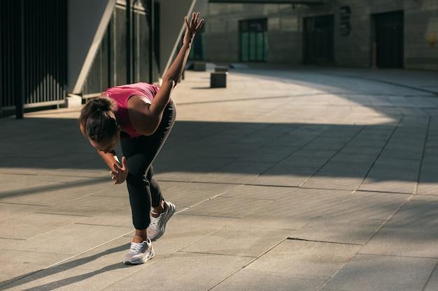 Giovane donna in abiti sportivi che si preparano per correre all'aperto e in piedi in una posizione speciale. modello banner