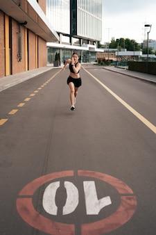 Giovane donna in volata al mattino all'aperto. vista dall'alto del corridore femminile che si allena in città.