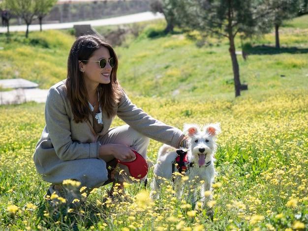 Giovane donna accovacciata con il suo cane schnauzer