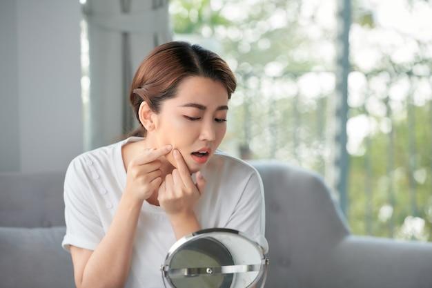 La giovane donna spremere la sua acne davanti allo specchio