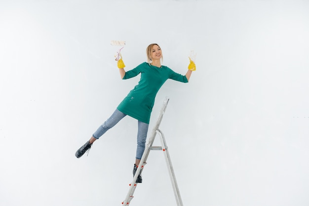 Una giovane donna sulle scale dipinge un muro bianco con un rullo