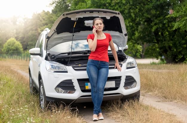 Giovane donna in piedi davanti a un'auto rotta e parla al telefono