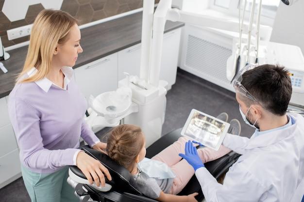 Giovane donna in piedi dalla sua piccola figlia seduta in poltrona dal dentista ed entrambi guardando i raggi x nel touchpad