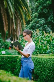 Giovane donna che sta all'università del campus con i libri di testo